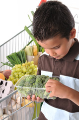 Cute boy checking broccoli isolated on white.