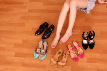 Closeup of a woman leg on floor and many shoes around
