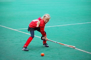 Field hockey girl poing to hit the ball