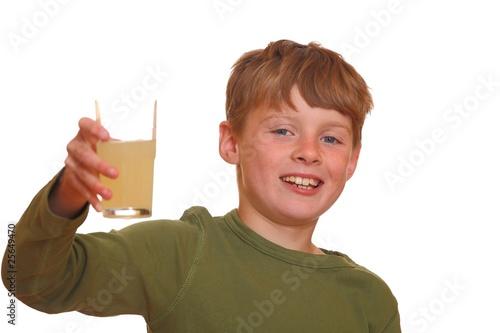 Leinwandbild Motiv Glücklicher Junge zeigt ein Glas voll Saft