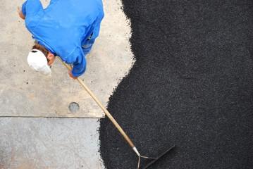 Bauarbeiter verteilt Bitumen auf der Straße