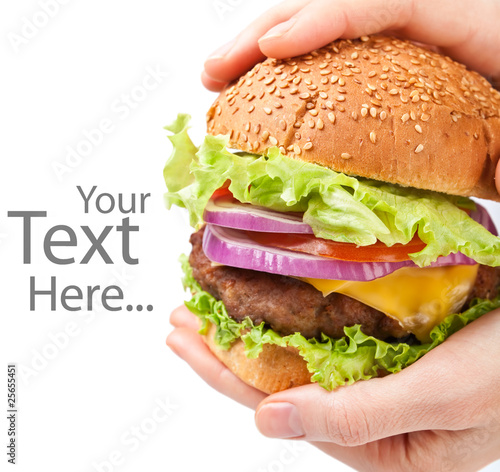 big cheeseburger held in hands with space for text
