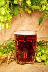 beer mug with hop and wheat on sacking still-life