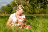 Fototapety Mutter stillt Baby auf Wiese