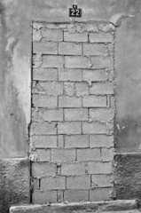 Bricked up door of abandoned building. Black and white.
