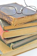 alte Bücher aufgestapelt und eine Lesebrille