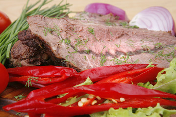 beef on wooden plate with peppers