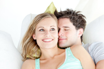 Portrait of a hugging couple sitting on a sofa in the living-roo