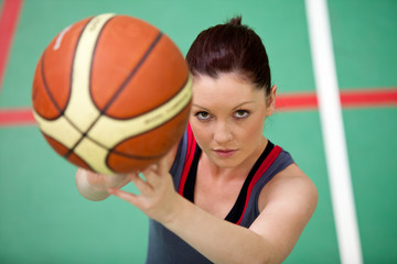 Portrait of an athletic young woman playing basket-ball