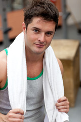 Handsome athletic man standing with a towel
