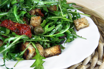 Rucola salad with dried tomatoes and pieces of tosts
