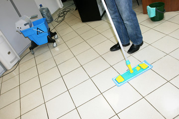 A man washing floor in the office with a swab
