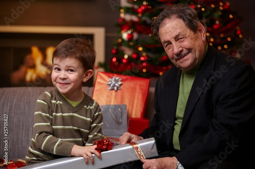 Grandfather and grandson wrapping gifts together