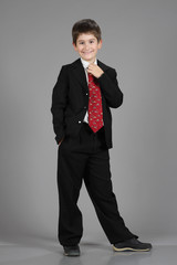 a boy dressed in black suit and red necktie ready for the shcool
