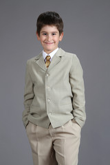 a boy dressed a beige suit and necktie ready for the shcool