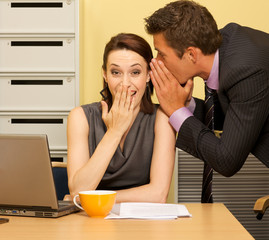 Businessman whispering in businesswoman's ear at office