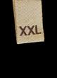 Macro of XXL size clothing label tag isolated on black
