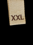 Macro of XXL size clothing label tag isolated on black