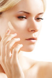 Cosmetology & cosmetic. Woman applying face skin foundation poster