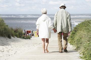 seniorenpaar auf dem weg zum strand