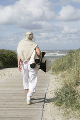 seniorin auf dem weg zum Strand