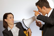 Businessman shouting at businesswoman through megaphone