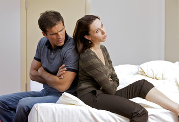 Young couple sitting back to back in hotel room