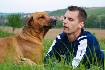 Young man and his dog in nature