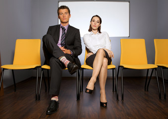 businessman and businesswoman sitting in waiting room