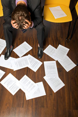 despeir businessman, documents scattered on floor