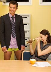 Businesswoman looking at businessman's underwear