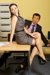 Businessman looking at woman sitting on table at office