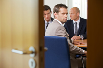 Businessmen in meeting while one looking at door