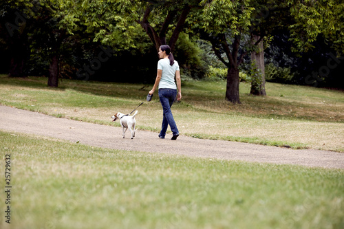 A young woman walking her dog in the park