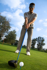 Man about to strike golf ball, low angle view