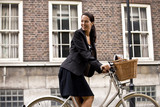 A businesswoman on a bicycle, smiling