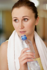 A young woman drinking a bottle of water