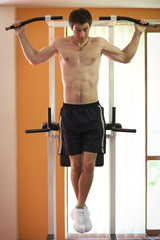 Man hanging on pull up bar