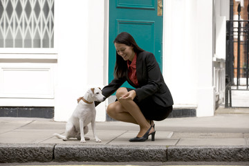A businesswoman giving her dog a treat