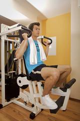 A young man exercising at gym