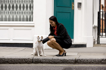 A businesswoman stroking her dog in the street