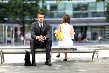 young caucasian businessman sitting on bench