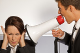 Businesswoman shouting at businessman through megaphone