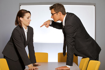 Businessman pointing towards businesswoman in office