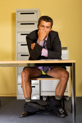 businessman sitting without pants at office, clenching fist