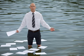 businessman standing in lake with papers floating on water