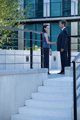 Businessman and woman shaking hands outside building