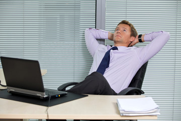 Businessman relaxing on chair with laptop on desk