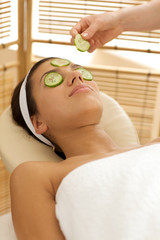 woman with cucumber slice being placed over eye
