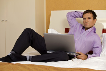 Portrait of young man with laptop on bed